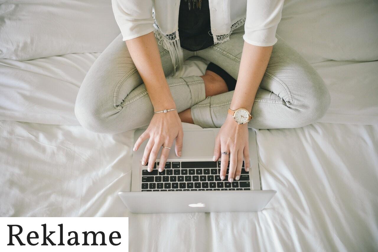 Kvinde sidder i seng med en computer